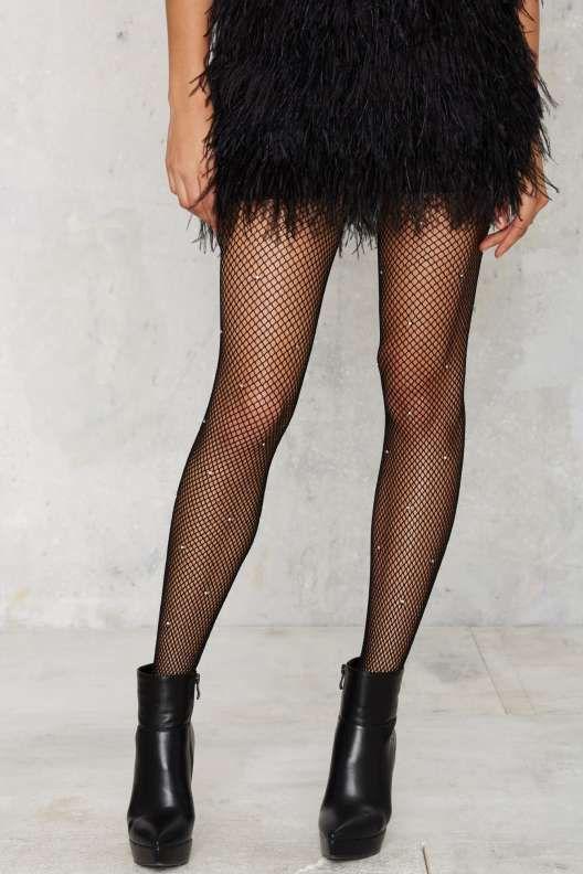 На девушке черное платье-мини с бахромой, чулки в сетку со стразами, черные кожаные ботинки на платформе и каблуке.
