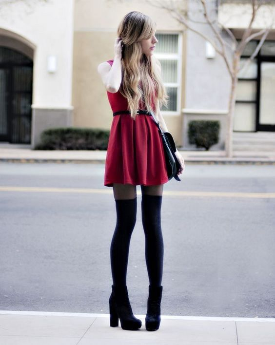 На девушке красное короткое платье с пышной юбкой, черные гольфы и ботинки на высоком каблуке.