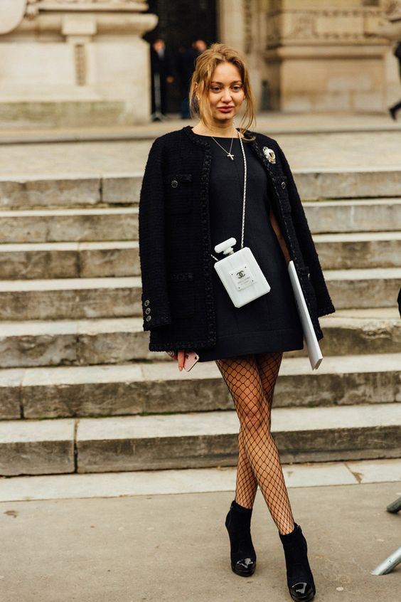 На девушке синее прямое платье-мини, оверсайз пиджак черного цвета, чулки в сетку, замшевые ботинки с лаковым носом.