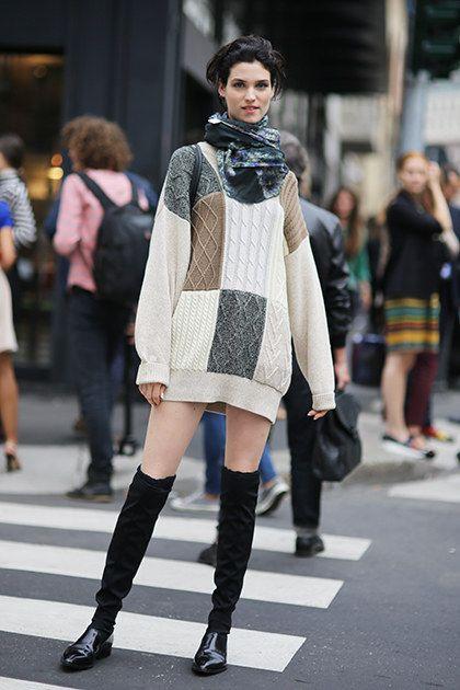 На девушке белый свитер-платье оверсайз в стиле пэчворк, лаковые туфли, черные свободные чулки.