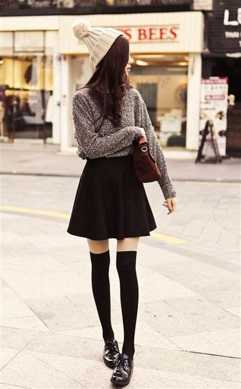 На девушке объемный серый свитер, заправленный в черную мини юбку-солнце с высокой талией, телесного цвета чулки, плотные черные чулки, лаковые черные оксфорды, коричневая сумка и бежевая шапка.