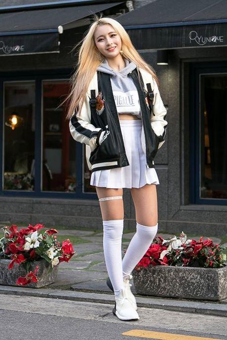 Серый укороченный свитер с надписью и капюшоном в сочетании с плиссированной белой юбкой-мини с завышенной талией, белыми плотными чулками немного выше колена, белыми кроссовками и черно-белым бомбером.