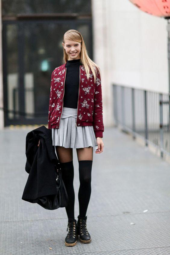 На девушке черная водолазка, серая юбка-мини, тонкие полупрозрачные колготки, плотные черные чулки, ботинки и бордовый бомбер.