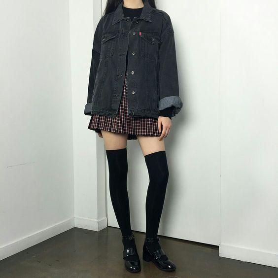 На девушке клетчатая юбка-мини, черные плотные чулки, лаковые туфли, серая джинсовая куртка.