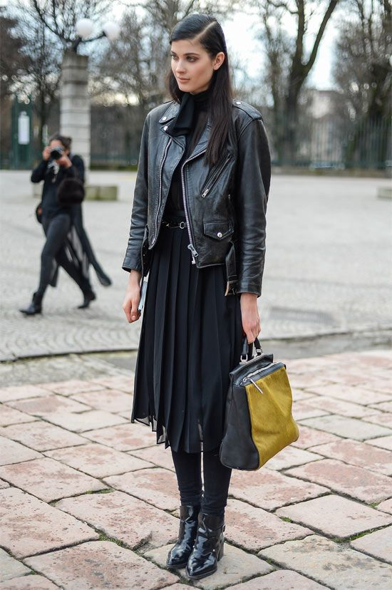 Черная водолазка, черная шифоновая плиссированная юбка ниже колена в сочетании с черными плотными чулками, лаковыми ботинками с заостренным носом, черной кожаной курткой и сумкой.