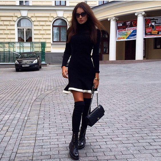 На девушке черный гольф, черная трикотажная юбка с белой полосой, плотные черные чулки и высокие ботинки.