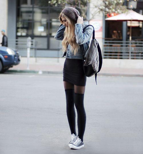 На девушке черная облегающая юбка-мини, джинсовая куртка, тонкие черные колготки, плотные чулки и кеды.