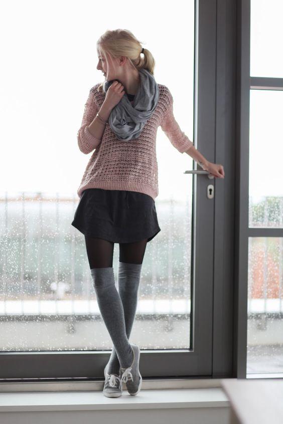 На девушке розовый свитер, черная юбка, серые плотные чулки и серые кеды.