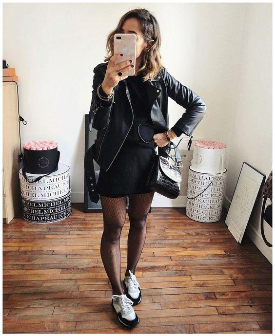 На девушке черное прямое платье-мини, чулки в сетку, черно-белые кроссовки, кожаная куртка и маленькая сумка.