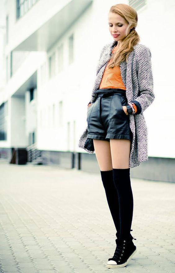 На девушке оранжевая блузка, кожаные черные шорты, телесные колготки, черные теплые чулки немного выше колена, черные высокие кеды и серый кардиган.