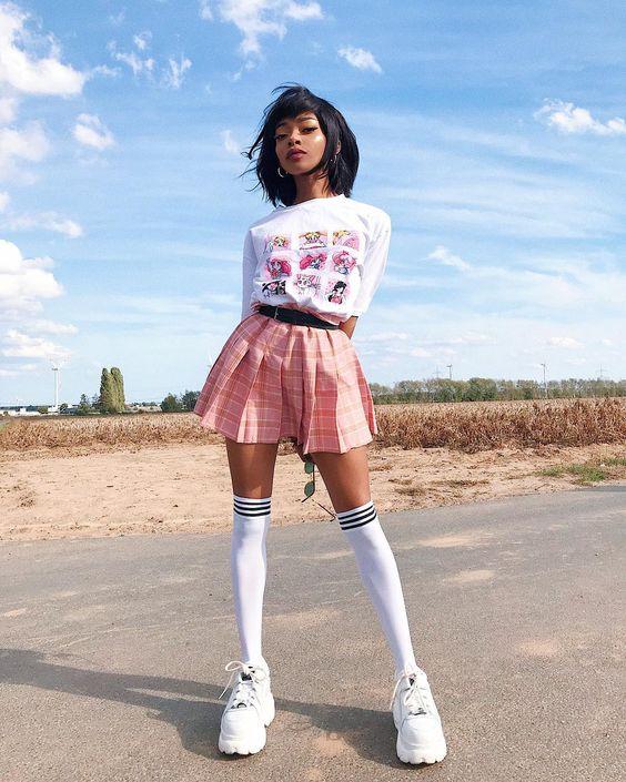 На девушке белая футболка с рисунком, розовая клетчатая юбка-мини с черным ремнем, белые массивные кроссовки, белые чулки выше колена.