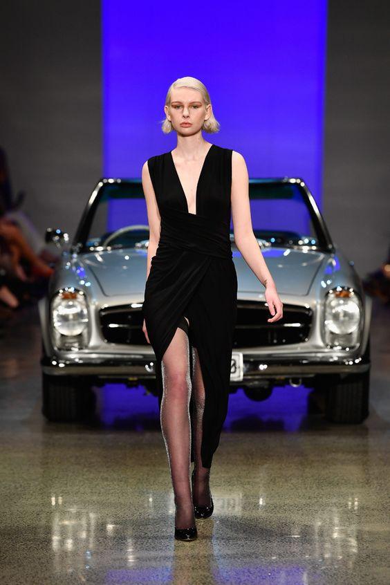 На девушке черное бархатное платье-миди с вырезом спереди и глубоким декольте, тонкие черные чулки из люрекса, лаковые черные лодочки на каблуке.