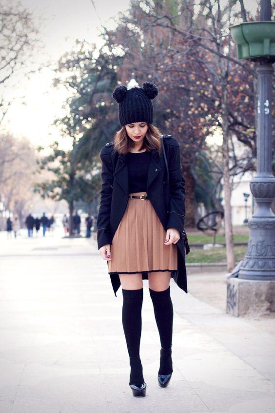 На девушке черный топ, светло-коричневая короткая юбка, плотные черные чулки и туфли на платформе.