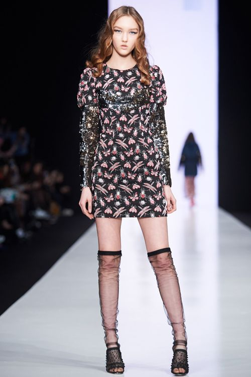 На девушке облегающее черное платье-мини с флористическим принтом и длинными рукавами, полупрозрачные черные чулки немного выше колена и черные босоножки в сетку на каблуке и с открытым носом.