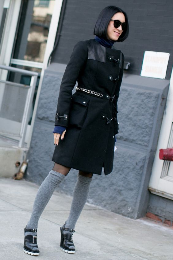 На модели черное пальто длиной до середины бедер, тонкие черные чулки, серые плотные чулки и босоножки на каблуке.