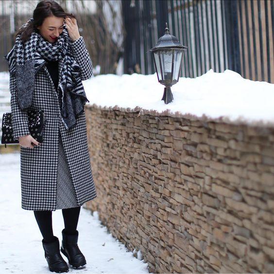 """На девушке черный свитер, прямая серая юбка ниже колена, плотные черные чулки, короткие кожаные угги, прямое пальто ниже колена с принтом """"гусиная лапка"""", длинный объемный шарф, черный клатч."""