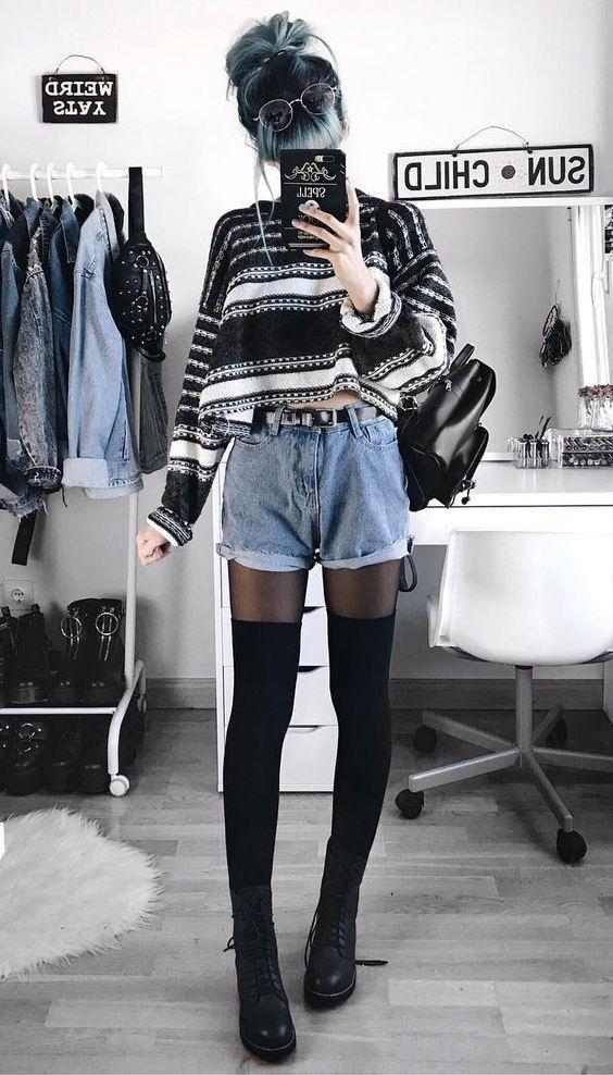 Черно-белый укороченный свитер в сочетании с голубыми джинсовыми шортами свободного кроя, тонкими черными полупрозрачными колготками, плотными черными чулками выше колена, кожаными ботинками на высокой подошве и на шнуровке, маленьким черным рюкзаком, очками.