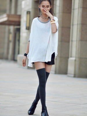 На девушке свободная длинная белая футболка, широкие кожаные шорты, плотные серые чулки выше колена, кожаные ботинки на плоском ходу. Образ дополнен аксессуарами.