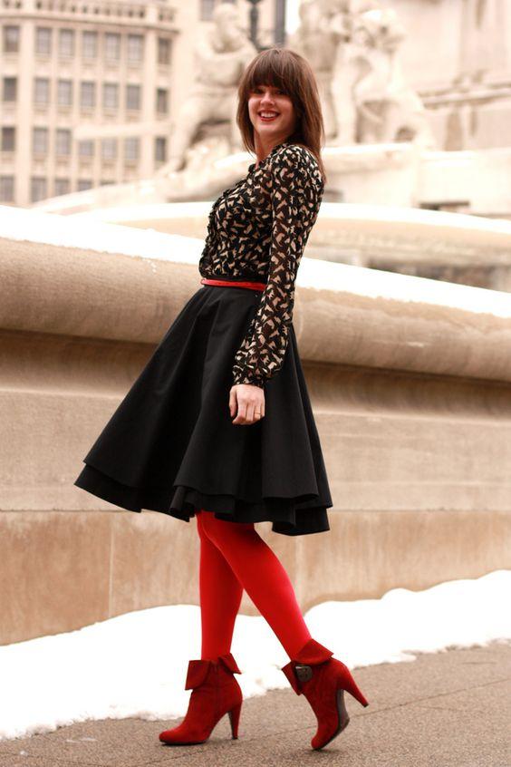 На девушке черная рубашка, черная пышная юбка, красные чулки и темно-красные ботинки на каблуке.