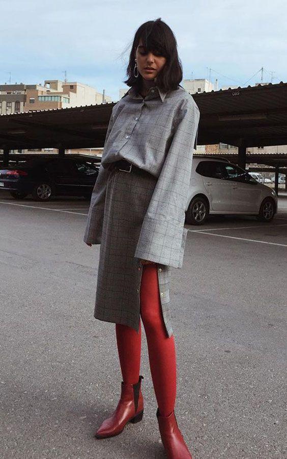 На девушке серая клетчатая рубашка с широкими рукавами, такая же юбка прямого кроя с разрезом, красные чулки и бордовые челси.