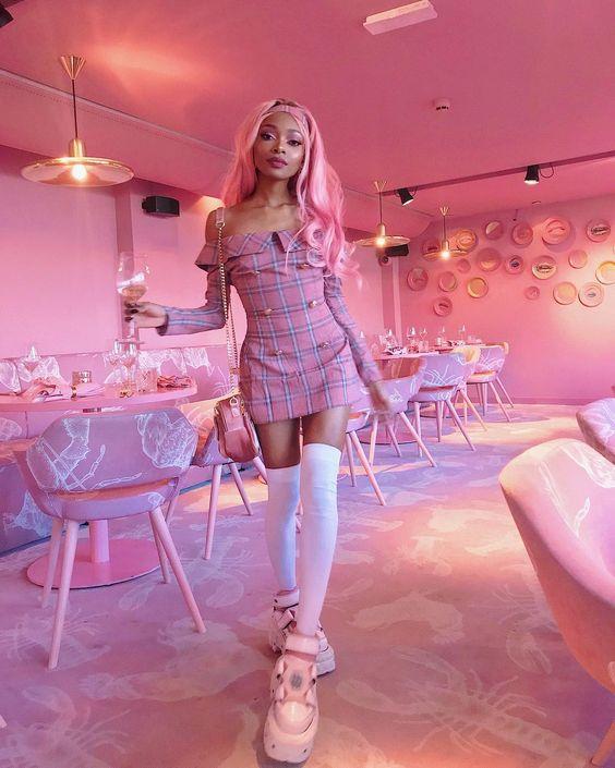 """На девушке розовое облегающее платье в клетку длины мини, с длинными рукавами, золотыми пуговицами и вырезом """"лодочка"""", белые плотные чулки выше колена, массивные розовые кроссовки на толстой подошве, маленькая поясная розовая сумка."""