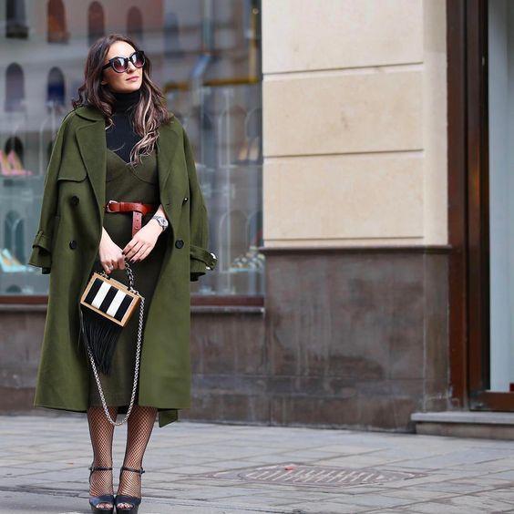 На девушке темно-зеленое платье-футляр длины миди с красным кожаным поясом, зеленое пальто, чулки в мелкую сеточку, темно-синие босоножки с открытым носом, на каблуке и платформе.