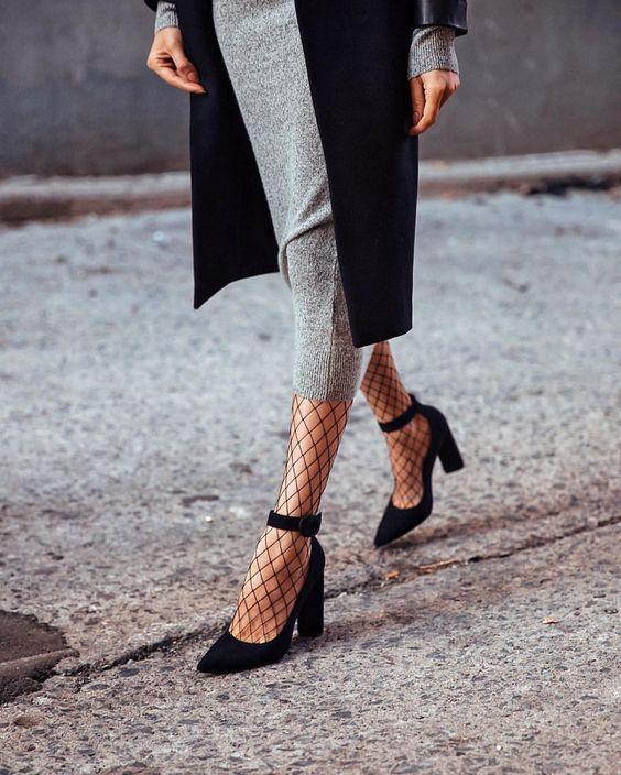 На девушке серое трикотажное платье-карандаш длины миди, чулки в сетку и туфли с заостренным носом и на каблуке.