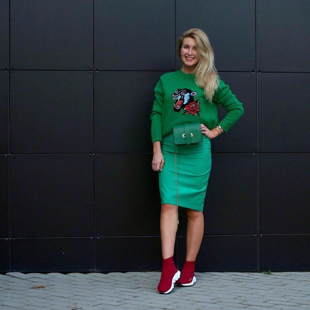 Красные кроссовки хорошо дополняют зеленый наряд.