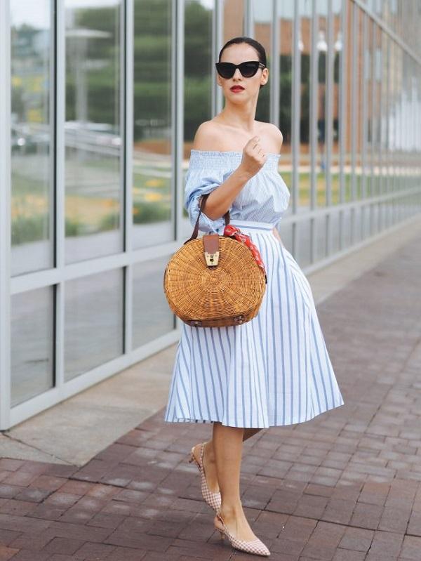 Для женственного образа наденьте кофту и юбку А-силуэта, туфли kitten heels и плетеный аксессуар.