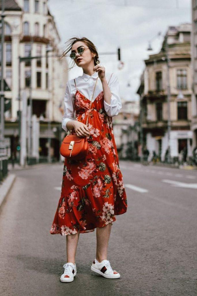 Сарафан на бретелях поверх рубашки — модный тренд. Красно-оранжевая сумка и белые кроссовки уместно дополняют аутфит.