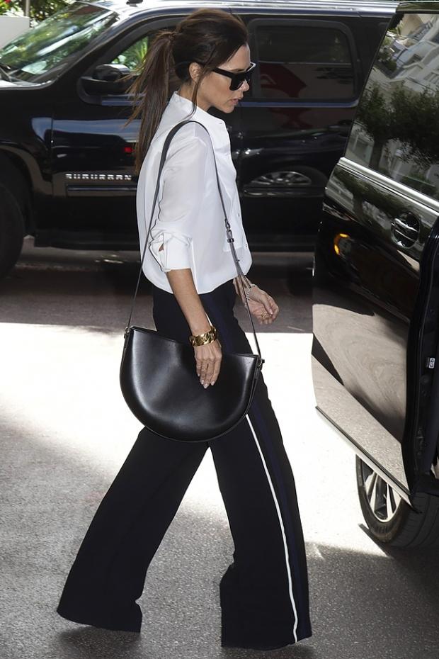 Виктория Бекхэм соединила в одном образе брюки клеш, светлую блузку и черную сумку-полумесяц.