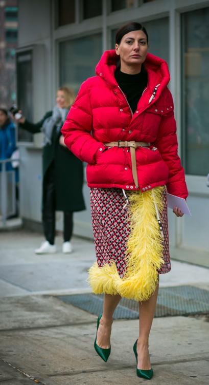 Красный пуховик до середины бедра, дополненный изящным ремешком, смотрится гармонично даже с экстравагантной юбкой, украшенной марабу