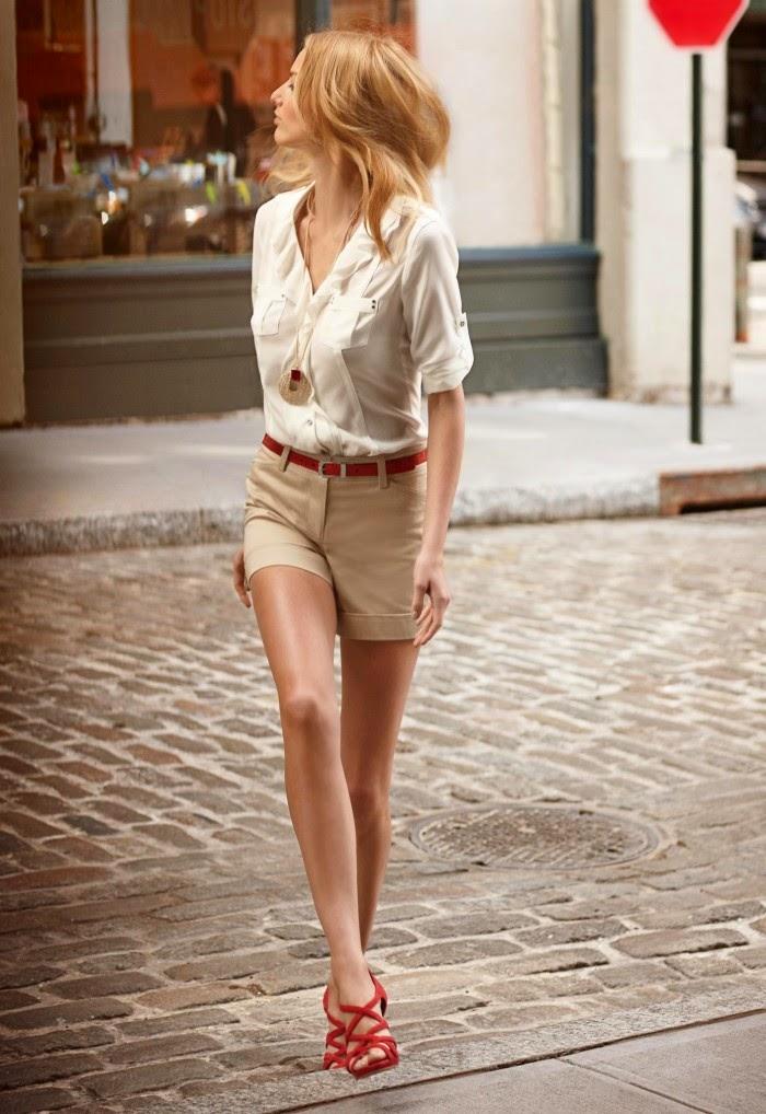 Молочно-белая блуза рубашечного кроя и шорты песочного оттенка смотрелись бы скучно без таких ярких акцентов, как красный пояс, созвучные с ним сандалии и красная вставка на кулоне