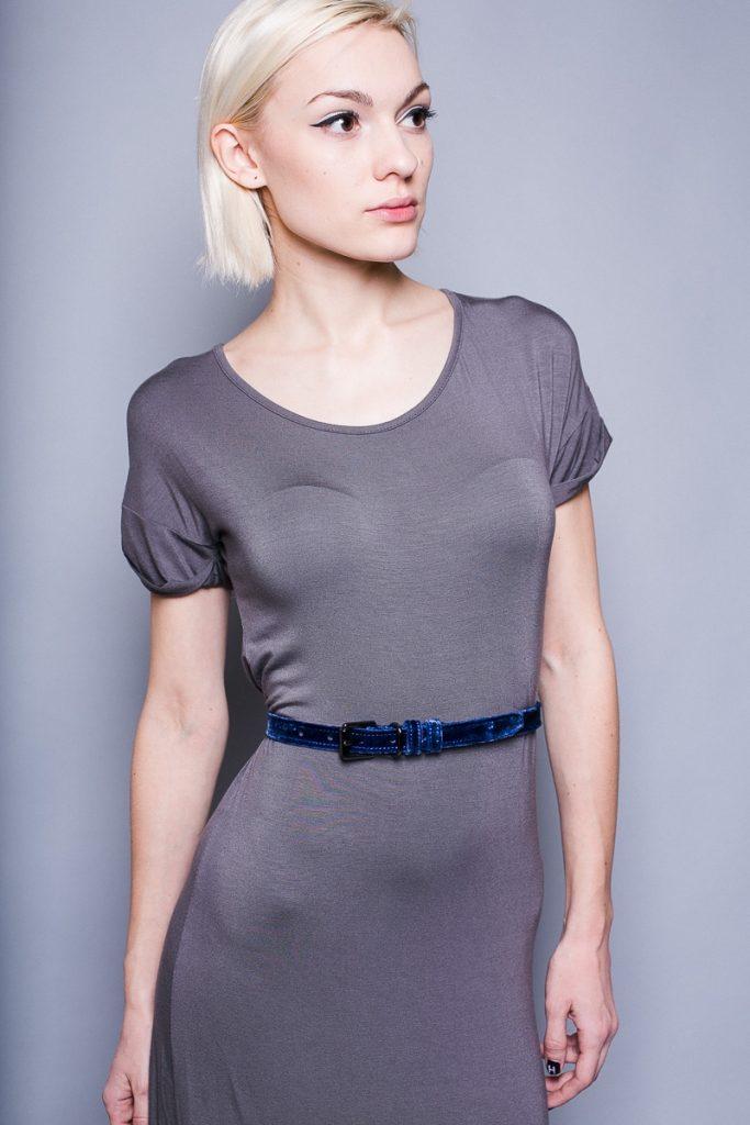 Узкий бархатный пояс выразительного оттенка ощутимо освежает серое трикотажное платье простого кроя