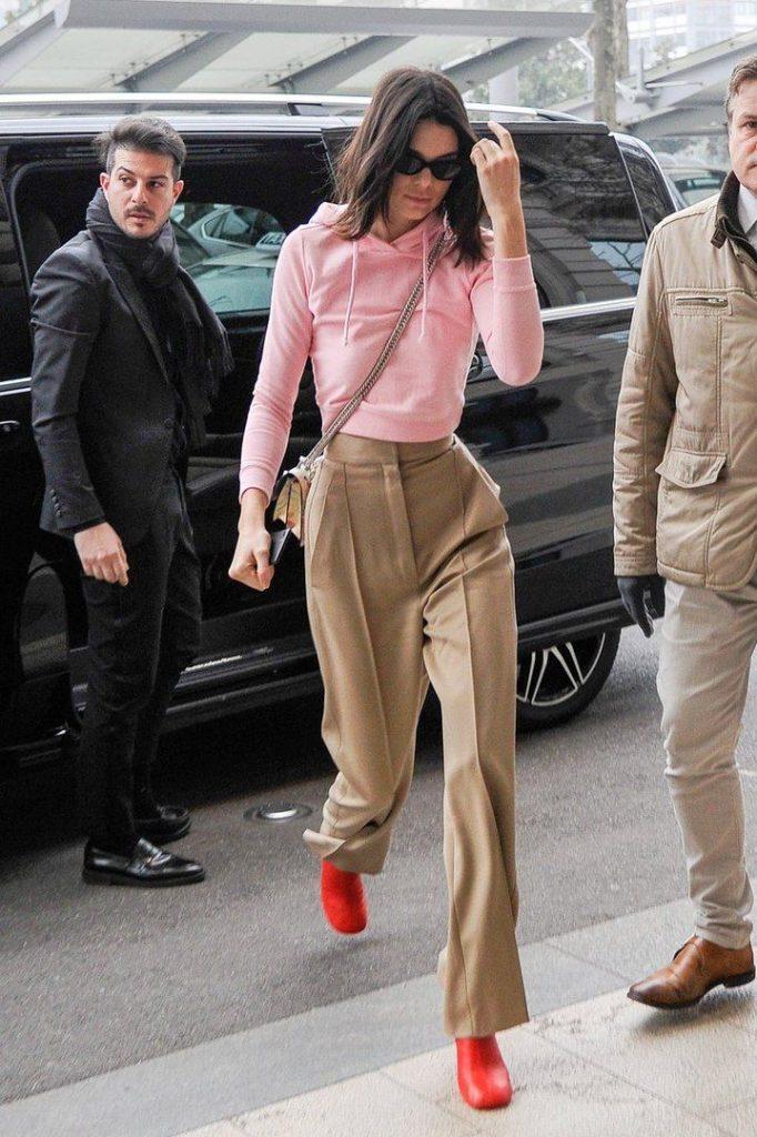Кендалл Дженнер надела брюки со стрелками, худи и красные полусапожки.
