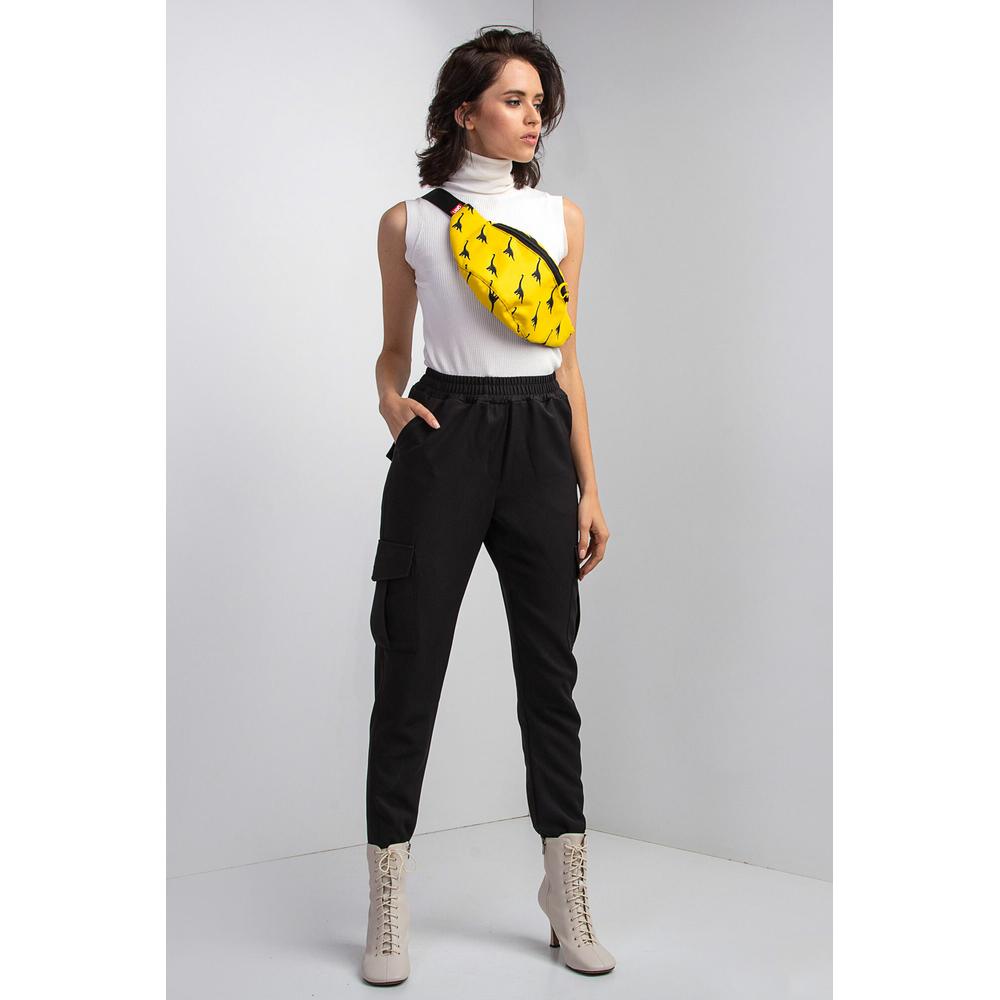 Сочетайте свободные штаны с кофтой, сапогами на каблуке и сумкой бананкой.
