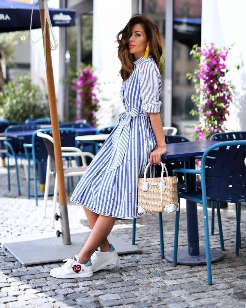 Расклешенное платье с кедами и плетеной сумкой — идея легкого женственного лука.